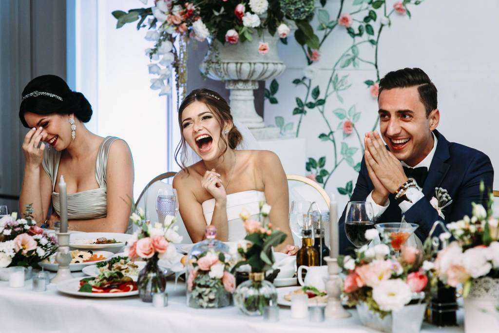 bride groom and bridesmaid laughing