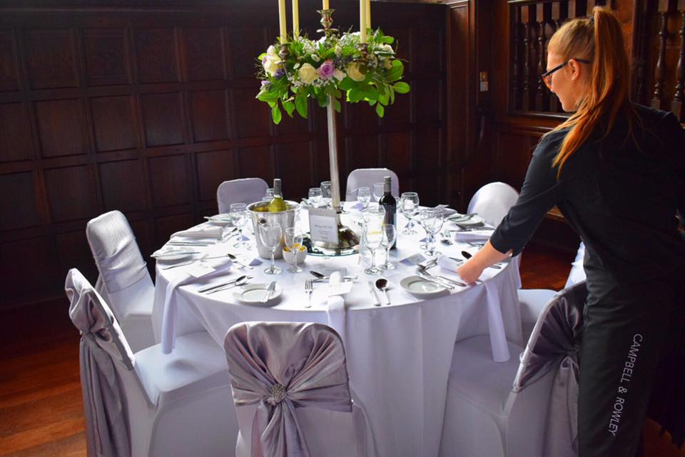 Campbell & Rowley waitress setting table at Hoghton Tower Banquetting Hall